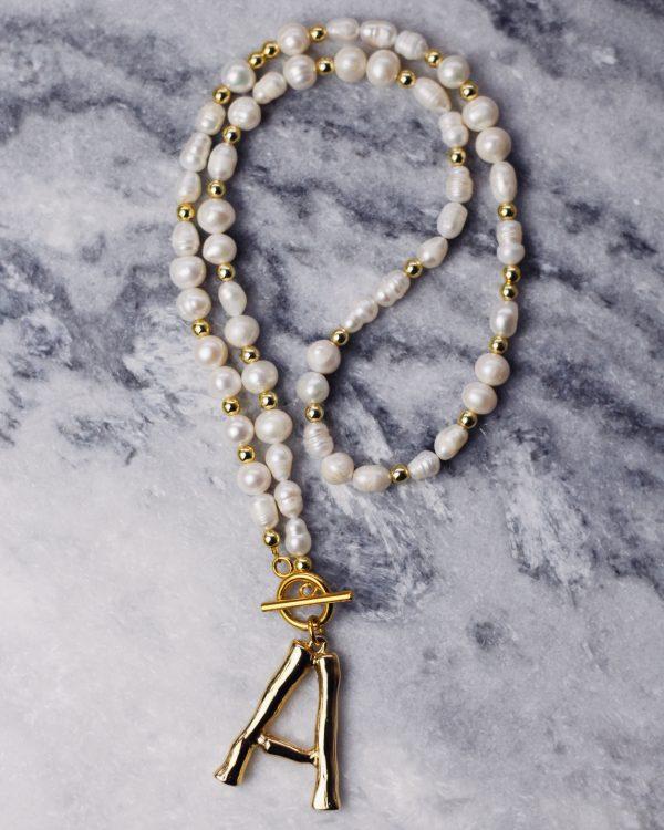 Upinių perlų ir raidės kaklo papuošalas